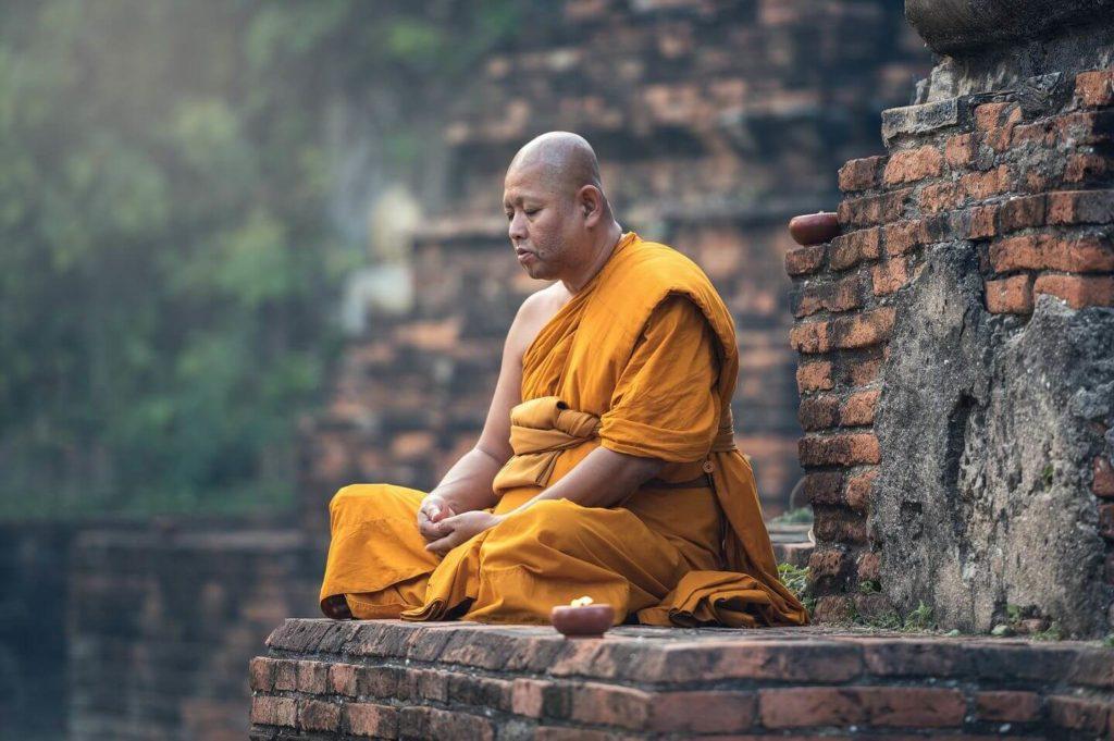 buddhist monk meditating in orange robes Thailand