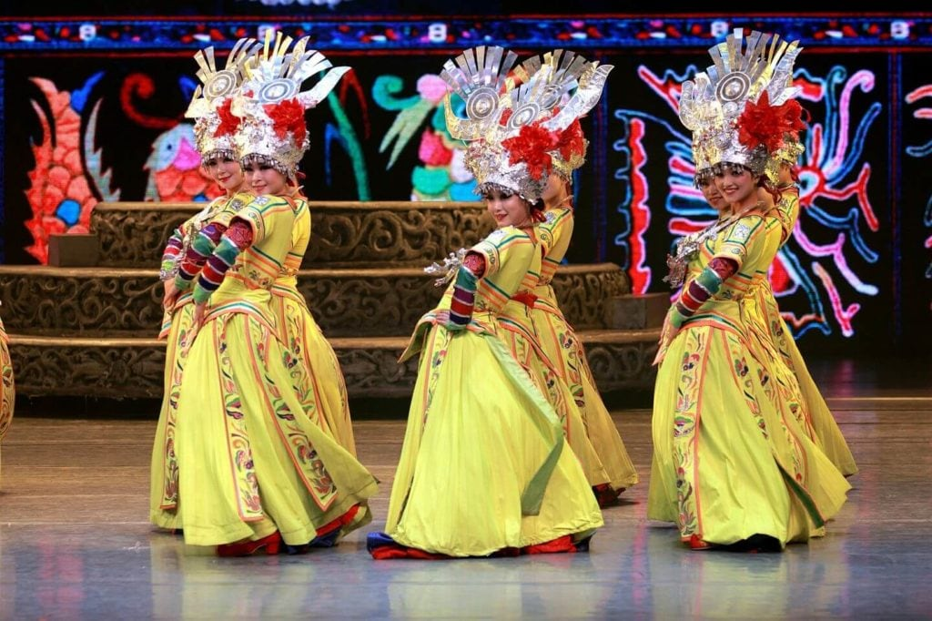 traditional dancers in bright costumes China travel guide