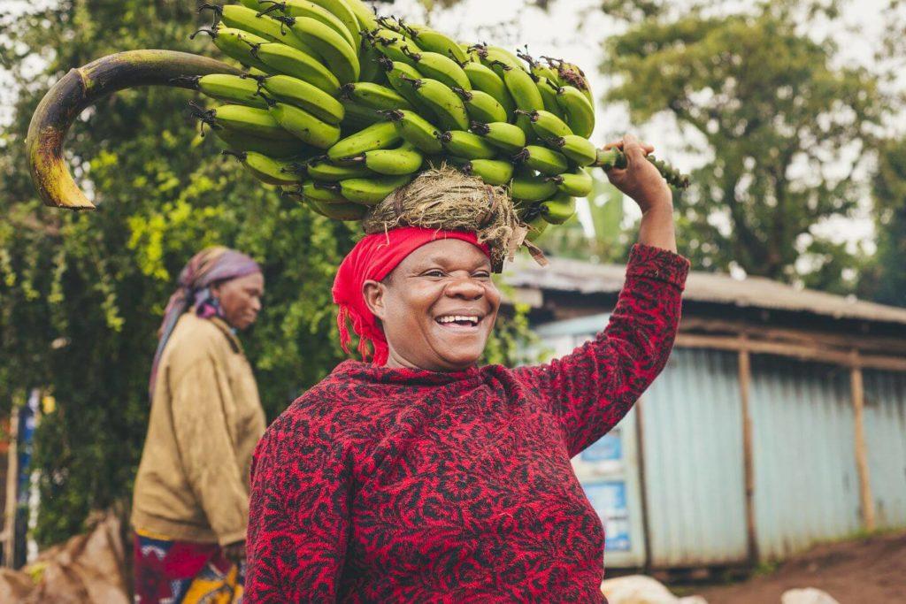 Tanzanian woman carrying bunch of bananas on her head Tanzanian culture