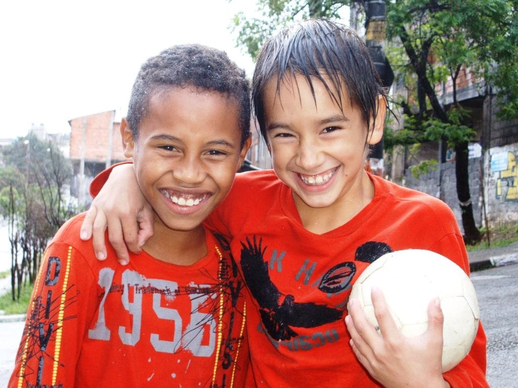 Young children posing with soccer or football in Brazil