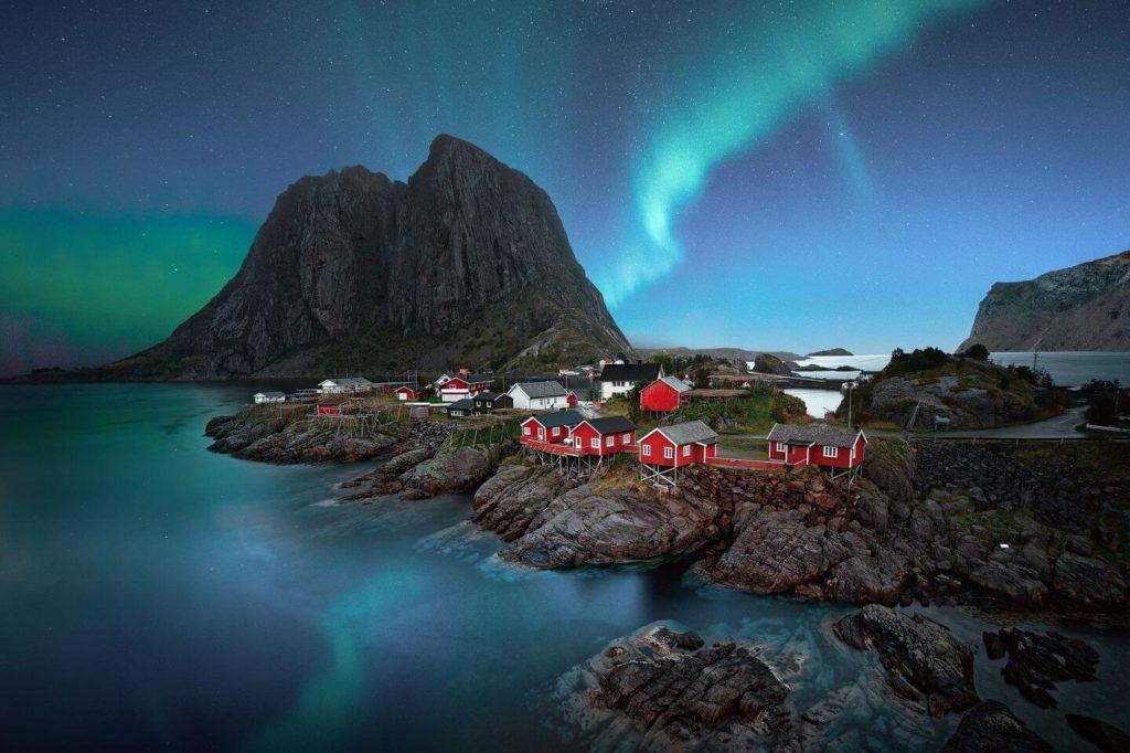 red cottages Northern Lights over rocky coastline Norway