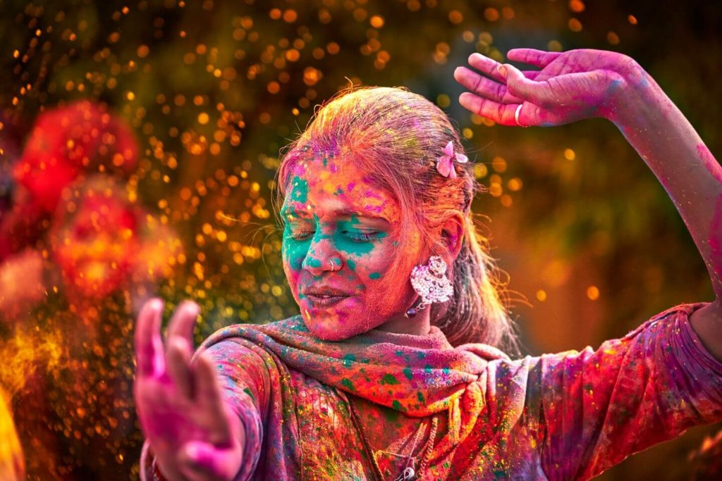 A woman covered in powered paint dancing outside at Holi festival.