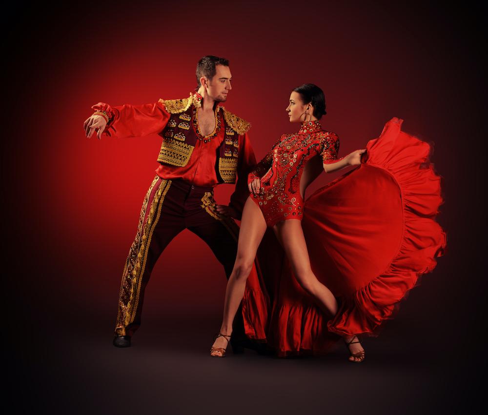 Professional rumba dancers posing the red costumes.