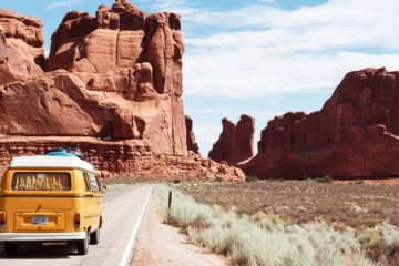 A yellow van driving with Utah's red cliffs in the background.
