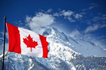 Canadian flag with snow covered mountains in the background.