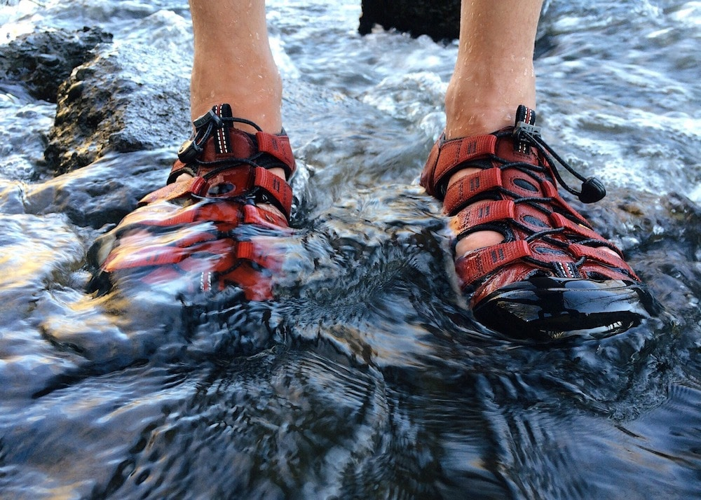Men's red hiking sandals in water.