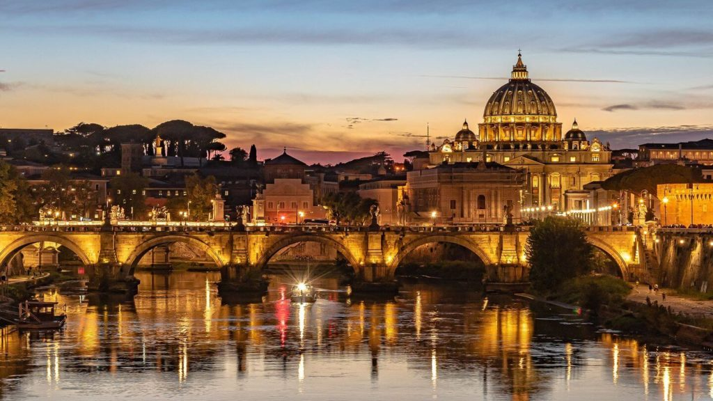 Rome bridge cathedral glowing at night