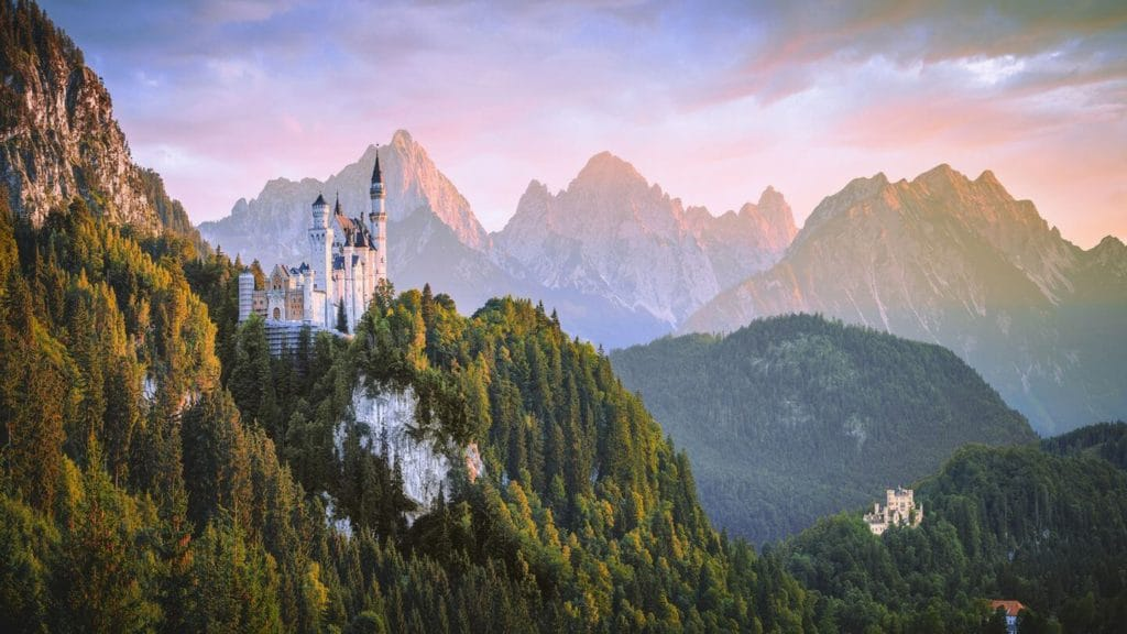 Neuschwanstein Castle rising out of the forested mountains Germany