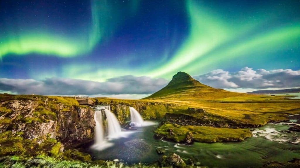 green northern lights over waterfalls and lush mountains Iceland