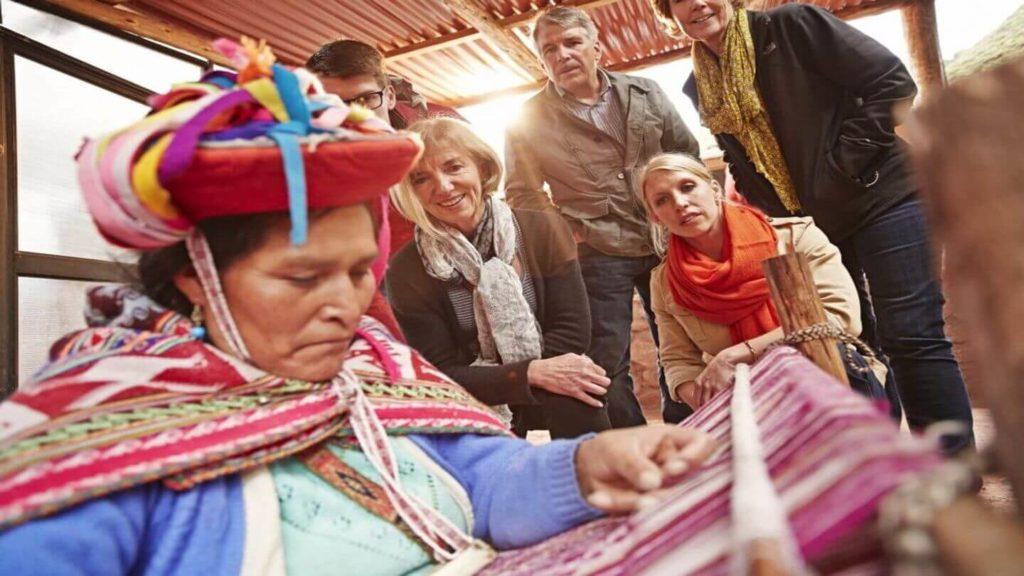 Trafalgar guests watching a Peruvian woman doing traditional weaving