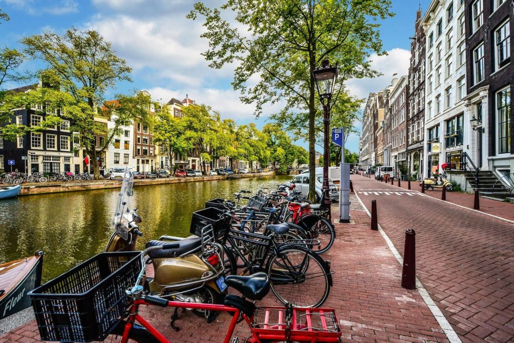 bicycles parked by a canal Amsterdam Netherlands