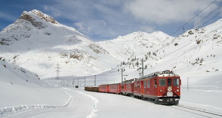 red Bernina Express driving through snowy mountains Switzerland