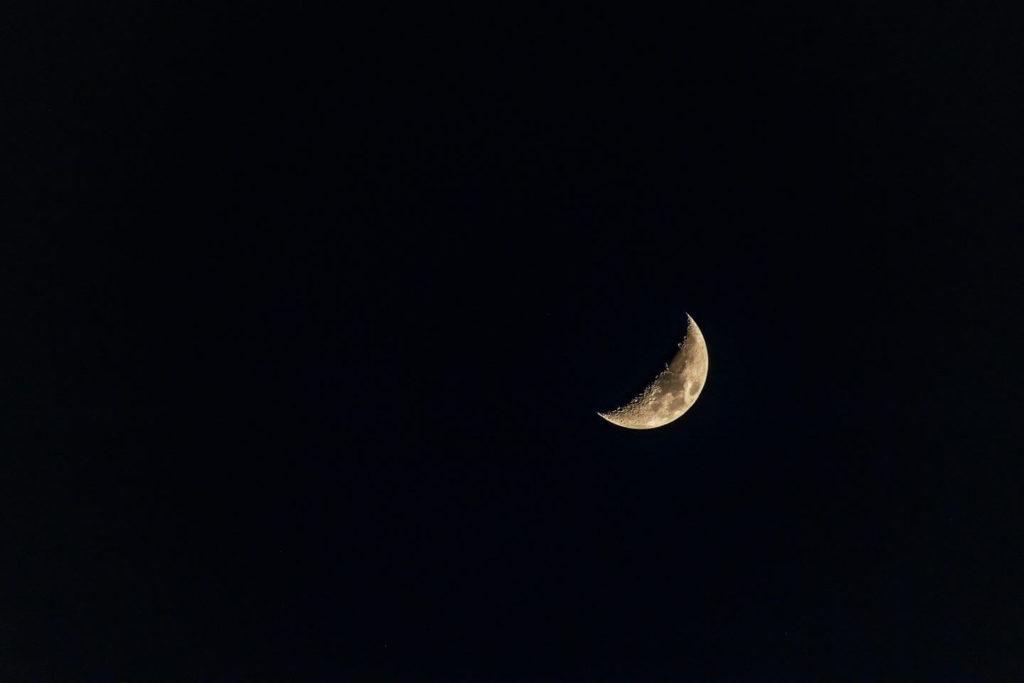 crescent moon in the dark night sky
