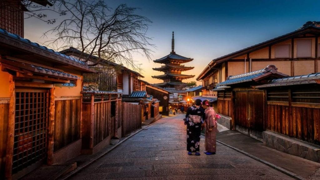 two women in kimonos in a traditional Japanese town at sunset