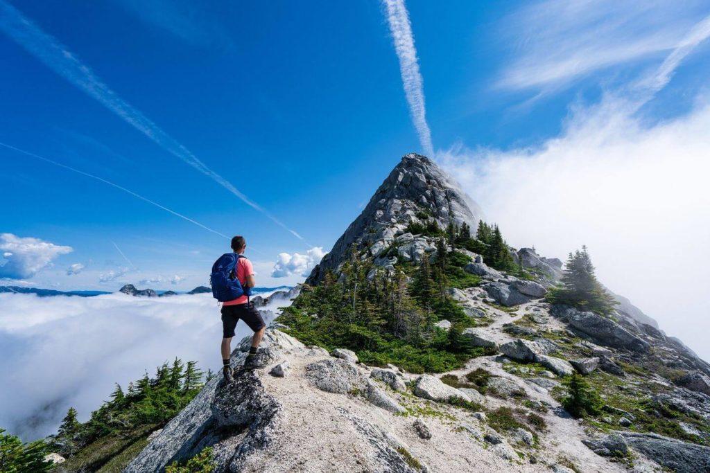 man hiking up a mountain peak