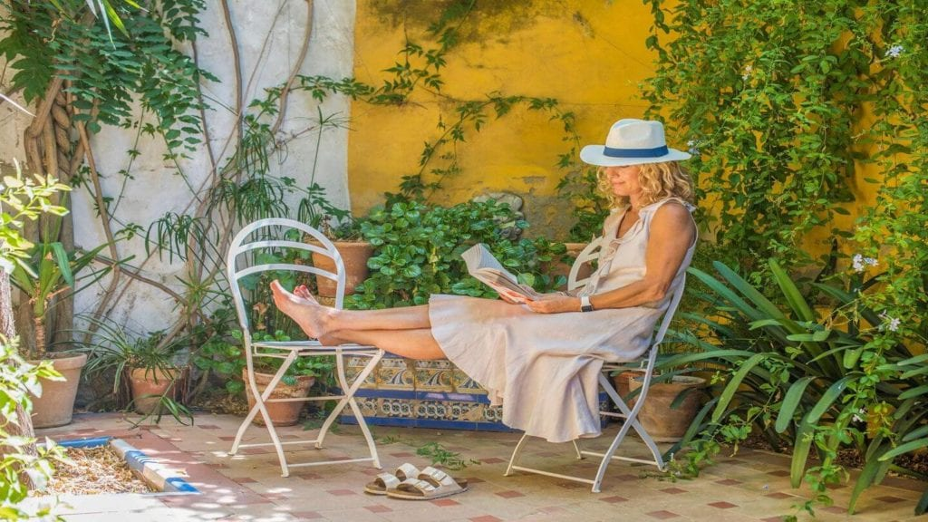 woman reading a book in a leafy courtyard