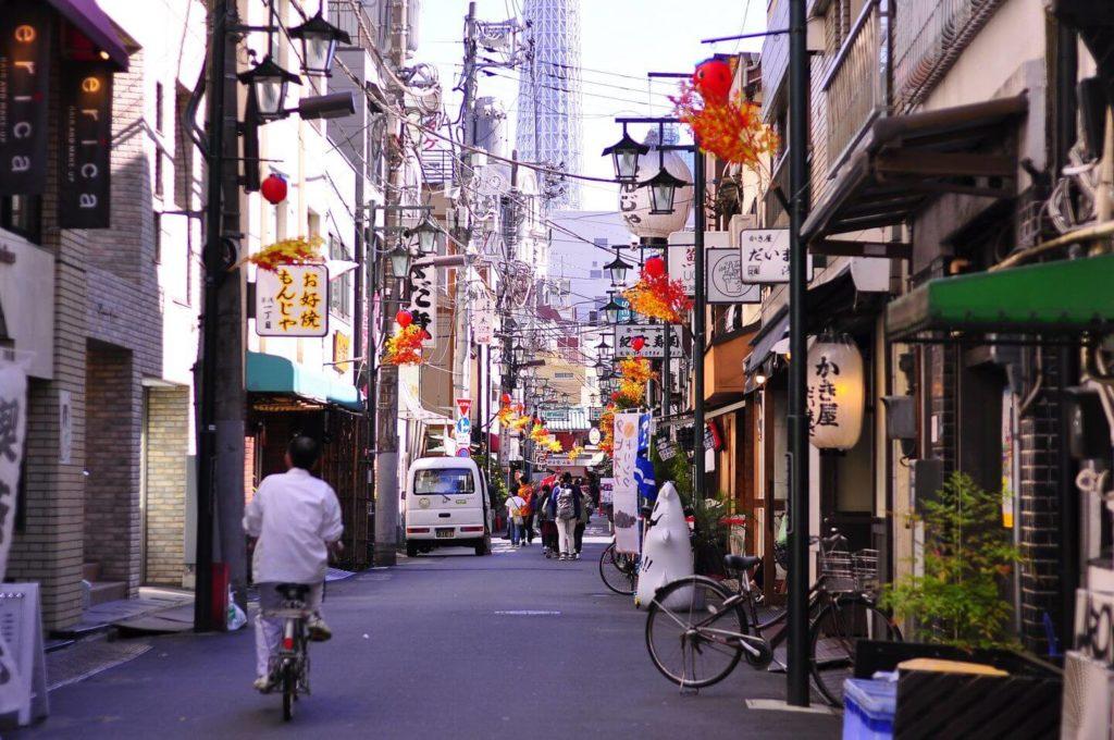 man cycling along a street in Tokyo Japan