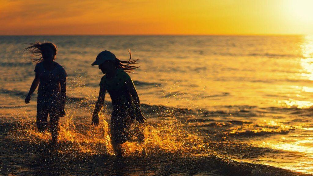 two girls splashing in the ocean at sunset
