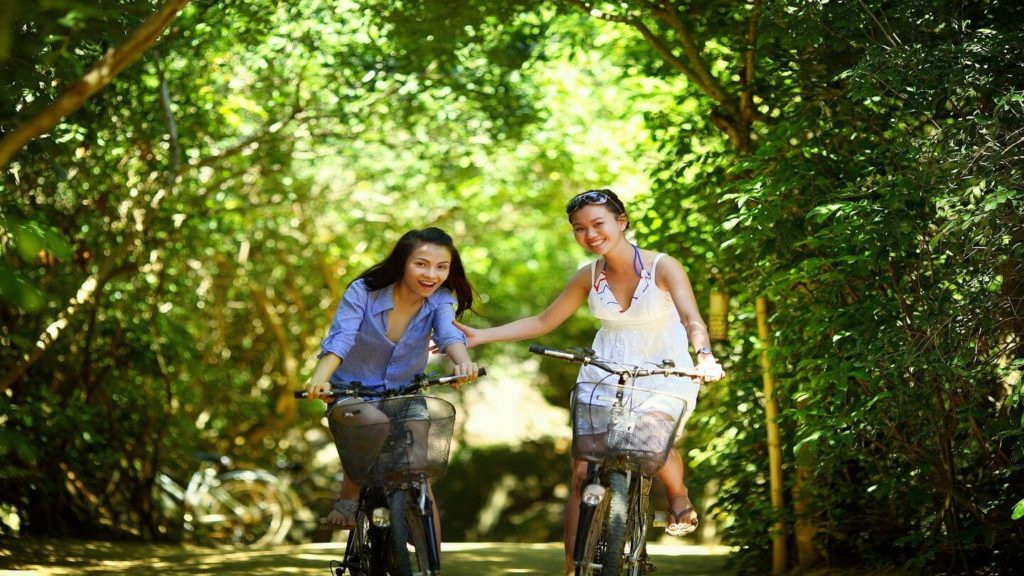 two women smiling and cycling down a leafy street