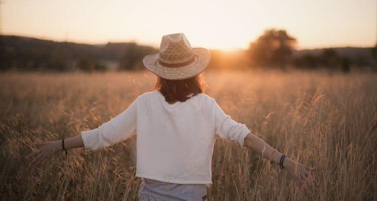 woman walking through a field at sunset travel reduces stress