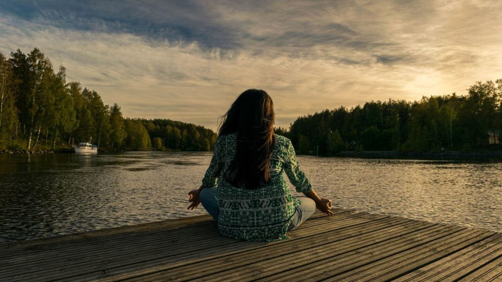 woman meditating on a deck at a lake