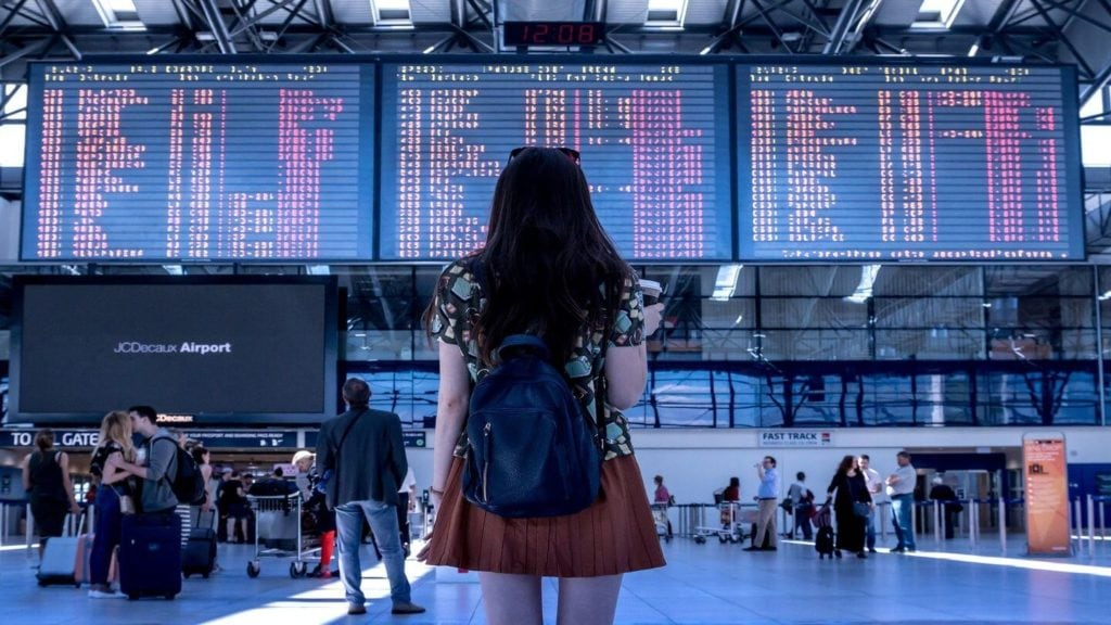 woman looking at departure boards in an airport