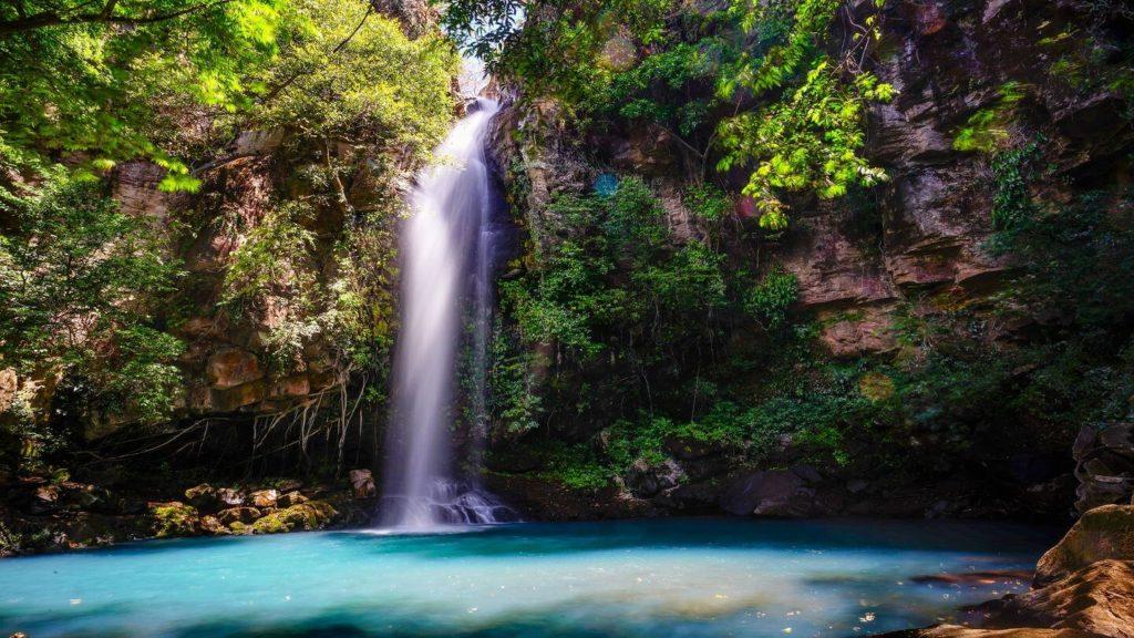 shimmering blue waterfall green jungle Costa Rica
