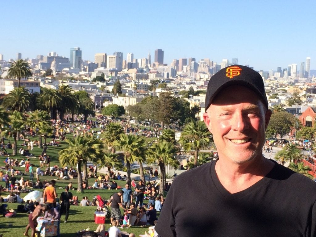 Stephen McNally in a US park, surrounded by people picnicking and palm trees
