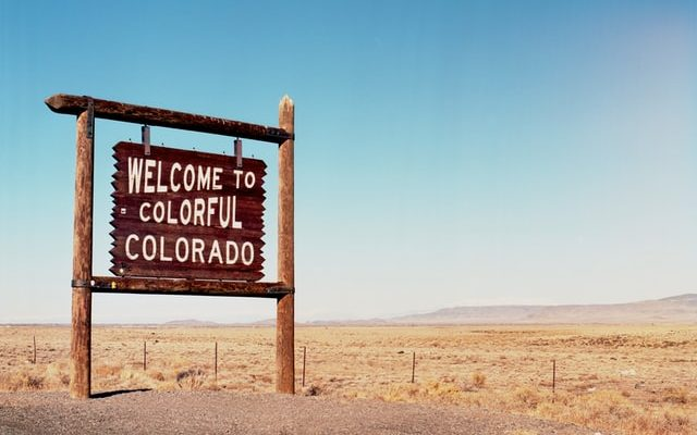 Sign in the sand that says 'welcome to colourful Colorado'