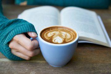hand holding coffee mug and book