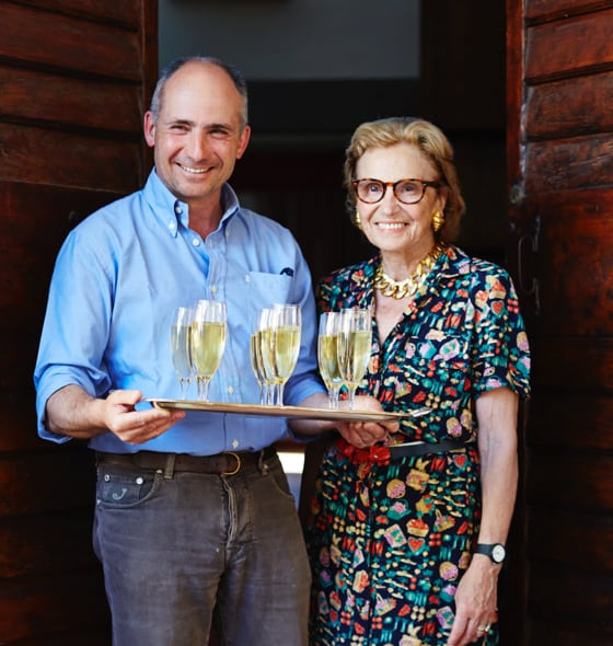 A man with a woman holding a tray of prosecco