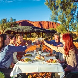 people toast Uluru trafalgar guided tours